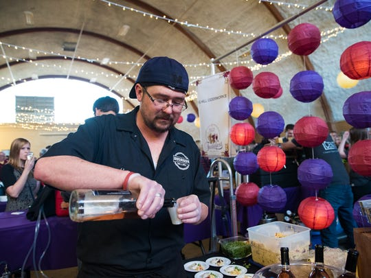 Alex Whitlow, of Blue Ridge Summit, Pa., chef for Bourbon Bar & Grill, pours a sample of bourbon house wine during the 2017 Tastefest of Hanover.