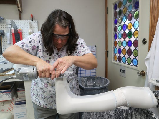 Michele Driggett, an orthotic technician with Spectrum Prosthetics & Orthotics Inc. works on a prosthetic leg Tuesday at the business in Redding. Owner Jeff Zeller recently moved the business from its Pine Street location because of crime in the area.