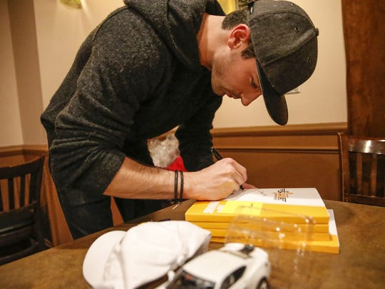 IndyCar driver Alexander Rossi autographs various materials for BorgWarner Inc., inside Dawson's on Main in Speedway, Ind., on Monday, March 6, 2017.