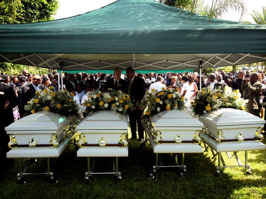 Damas family caskets under a tent before the burial ceremony for Guerline Damas and her five children at Palm Royale Cemetery in North Naples in 2009. Guerline and her oldest son, Meshach, 9, were alone in their caskets, but Maven, 6, and Morgan, 1, were buried together, and Marven, 5, and Megan, 3, also were buried together.