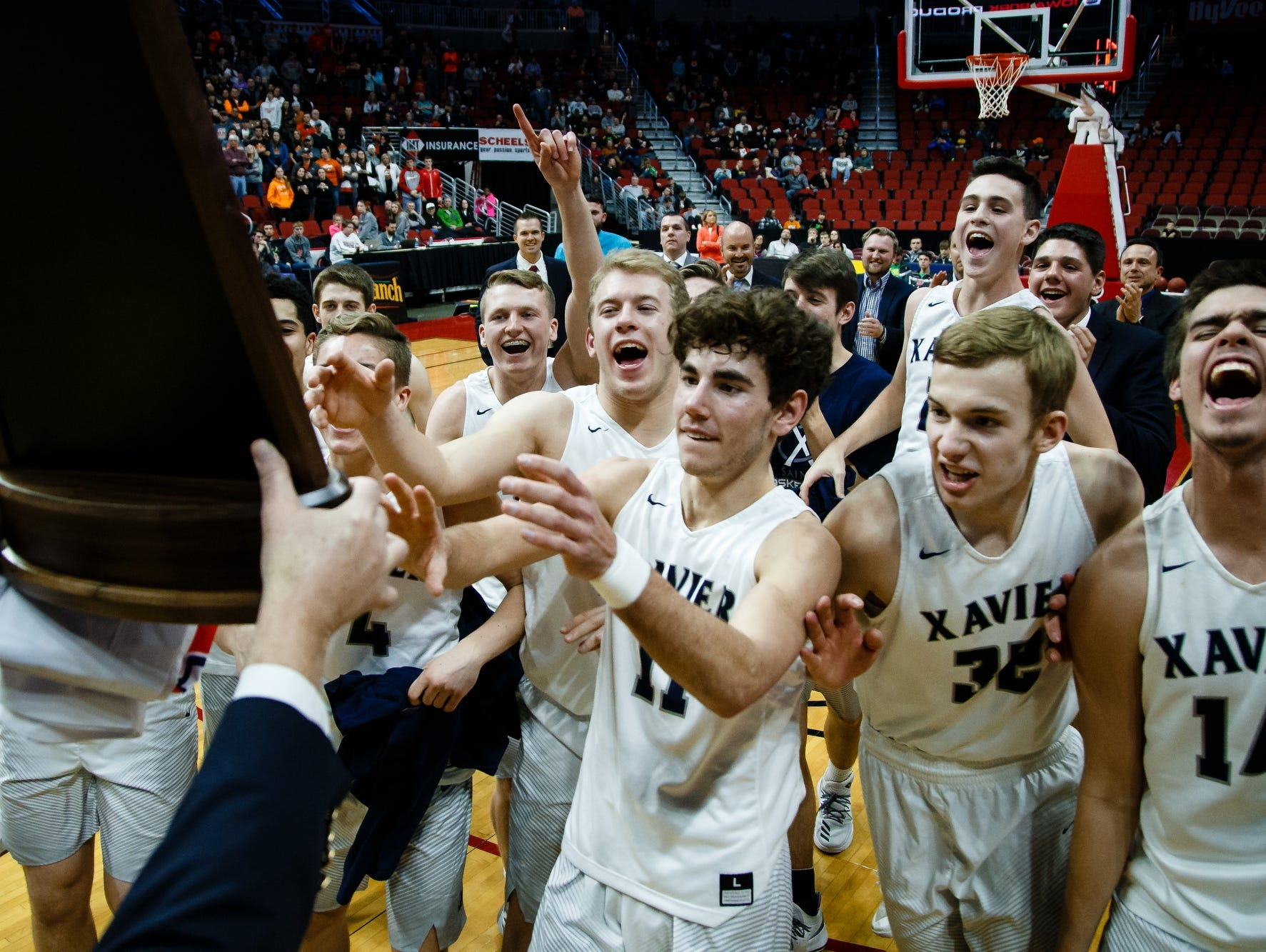 Cedar Rapids, Xavier gets their trophy after defeating Sergeant Bluff-Luton during their 3A state basketball championship game on Saturday, March 11, 2017, in Des Moines. Cedar Rapids, Xavier won 54-49.