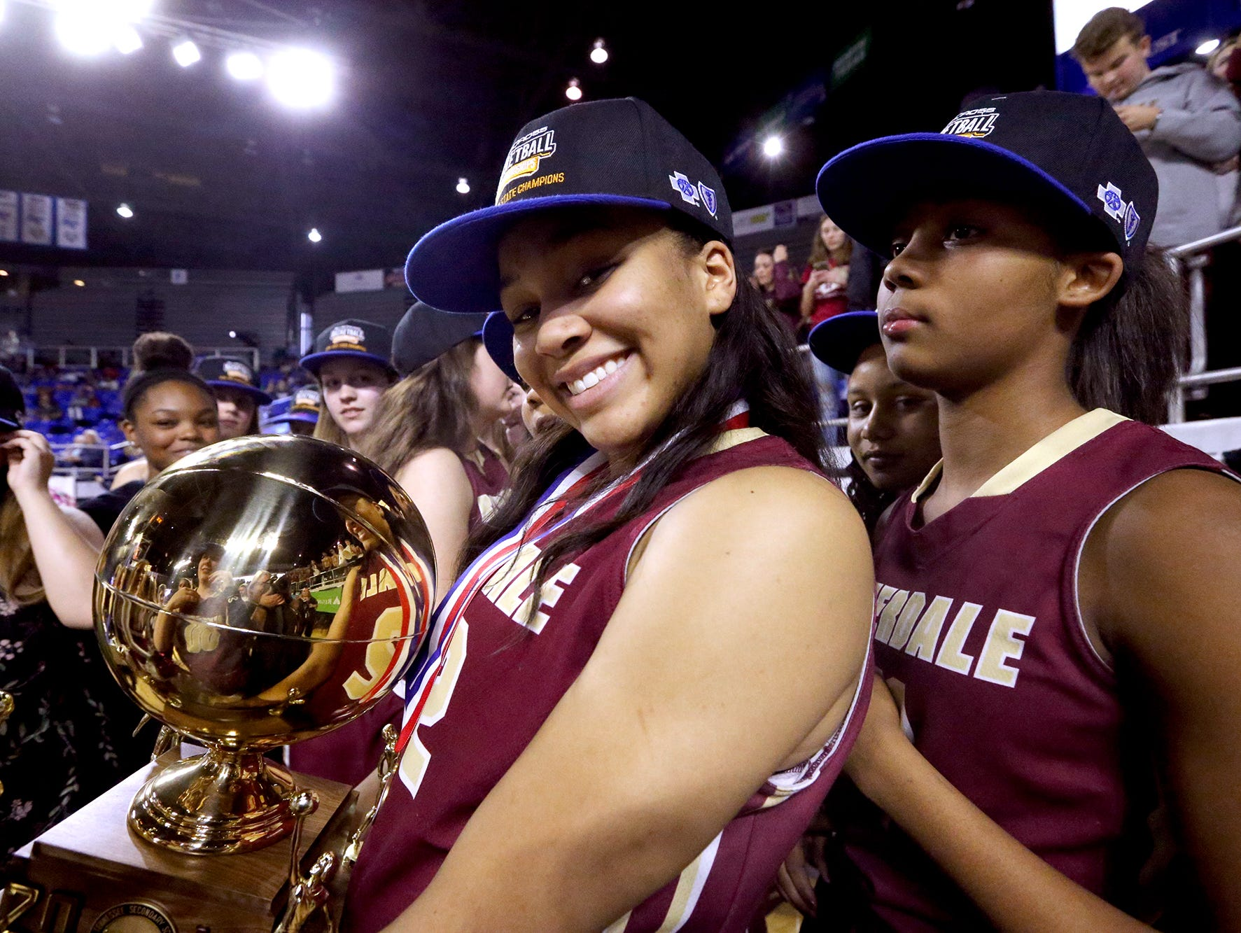 Riverdale's Brinae Alexander (32) holds the championship trophy with her teammate Aislynn Hayes (11) behind her as the team celebrates their victory over Memphis Central in the Class AAA final on Saturday, March 11, 2017.
