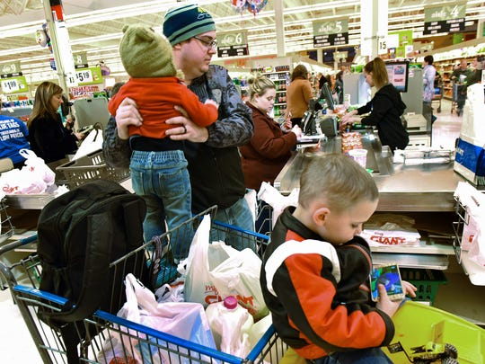 Dale and Tiffany Stangle and their kids, Asher and Axel, right,  get groceries at Giant Food Store at Norland Avenue, Chambersburg, on Monday, March 13, 2016. Customers are loading up on food in anticipation of this week's snow storms.