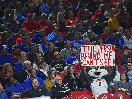 The USD mascot holds up a sign in front of SDSU fans during a game at the Sanford Coyote Sports Center.
