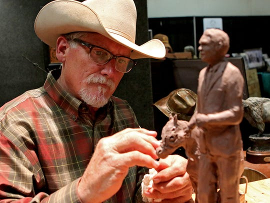 Artist John Rule works on a model for a sculpture he's