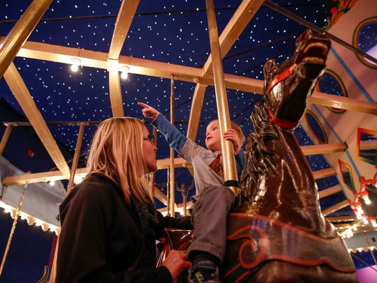 Kristen Warzon rides the carousel at the Children's