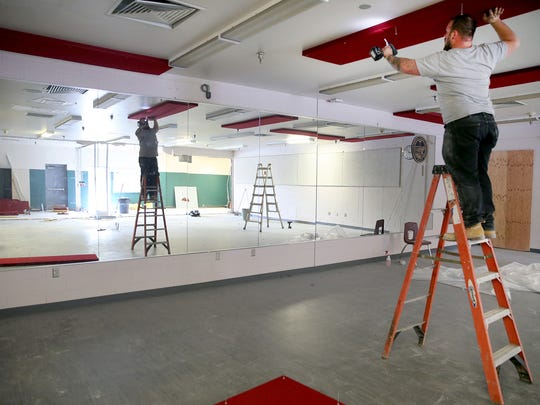 Panels are taken down in the old fitness room to be transformed into a locker room at Klahowya Secondary School.