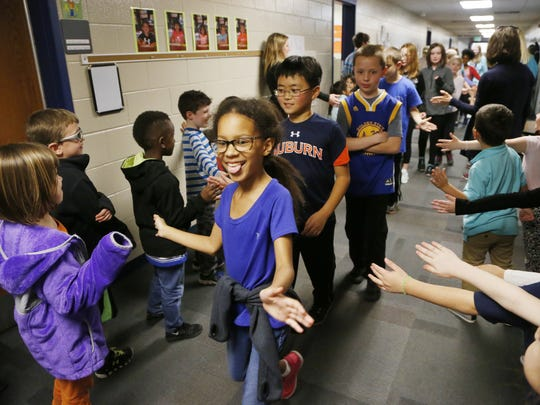 Kindergarten, first- and second-grade students line the halls to exchange high fives and encourage third-, fourth- and fifth-graders as they prepare to takes ISTEP tests last February at Klondike Elementary School in Lafayette.