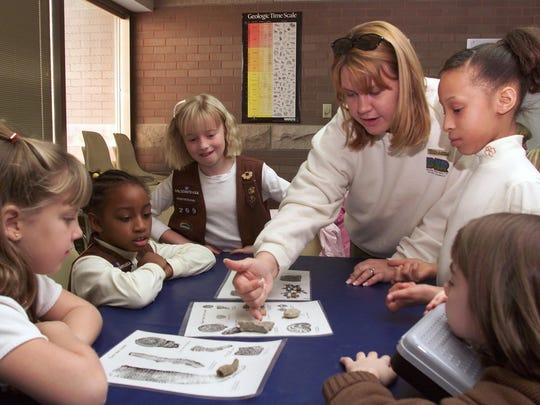 At a Girl Scouts Festival of the Arts workshop at Falls of the Ohio State Park in Clarksville, Ind., naturalist Crystal Smith points out fossils.