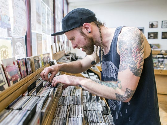 Local musician Justin Miles, who makes music under the name Luzius Stone, searches through CDs at Harvest Records in West Asheville, April 9, 2015.
