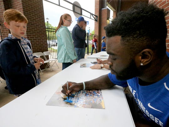 MTSU basketball player Giddy Potts signs a poster for