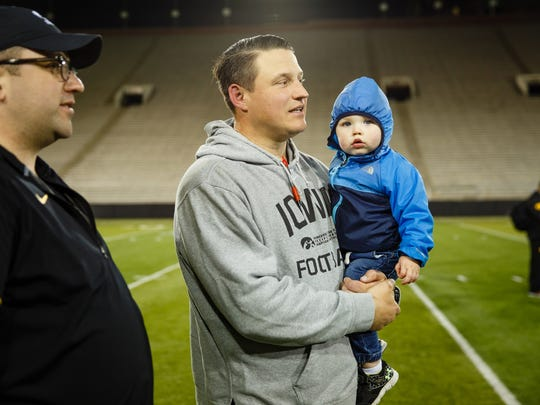 Iowa offensive coordinator Brian Ferentz walks off the field with his son after their Spring Game on Friday, April 21, 2017, in Iowa City.