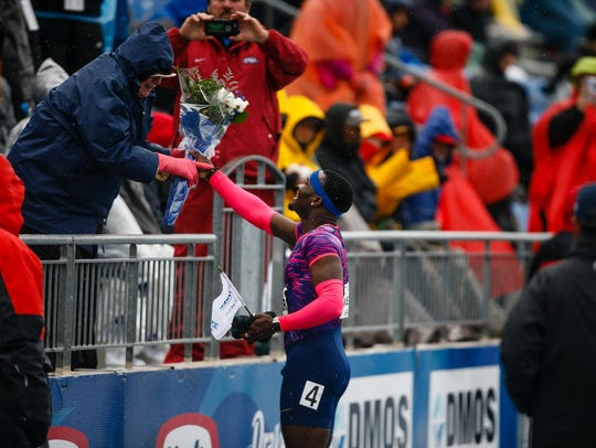 Omar McLeod gives flowers to a fan in the stands after