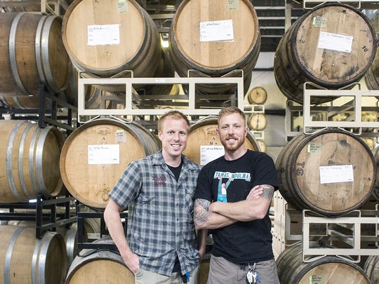 Nick, left, and Walt Dickinson, owners and brewers of Wicked Weed, stand in front of barrels inside their new Funkatorium on Coxe Avenue in Asheville in 2014.