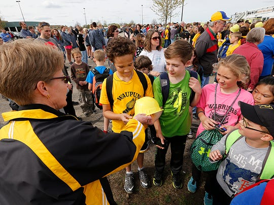 Waupun Junior/Senior High School Physical Education Teacher Becky Smith hands out plastic hard hats to Rock River Intermediate sixth-grader Zechariah Abernathy and Waupun seventh-grader Landen Krohn Wednesday during the Waupun School District's ground breaking ceremony for their new sports complex.