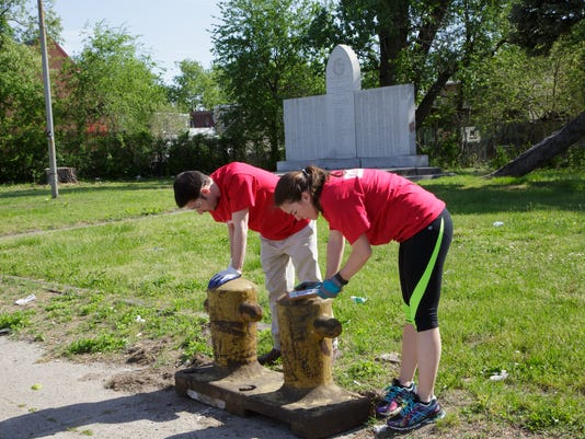 636296272069145849-8th-ward-memorial-park-Campbell-Soup-employees-scrape-rust-from-bollards-on-make-a-difference-week.jpg