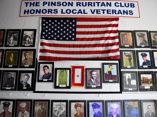 """Photos of veterans line the """"Wall of Honor"""" inside the old Pinson School."""