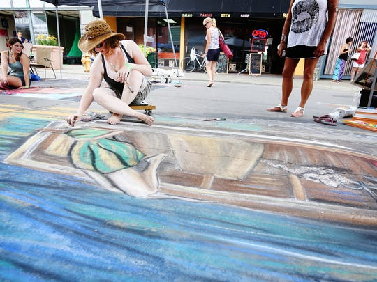 Crystal Parks works on her chalk subject at the 2015 Elmira Street Painting Festival. The Erin resident won first place overall for her original piece, which portrays a woman laying in a boat.