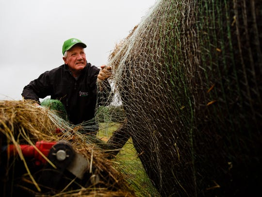 Farmer and Ranchers Ron Crumly cuts netting on a hay