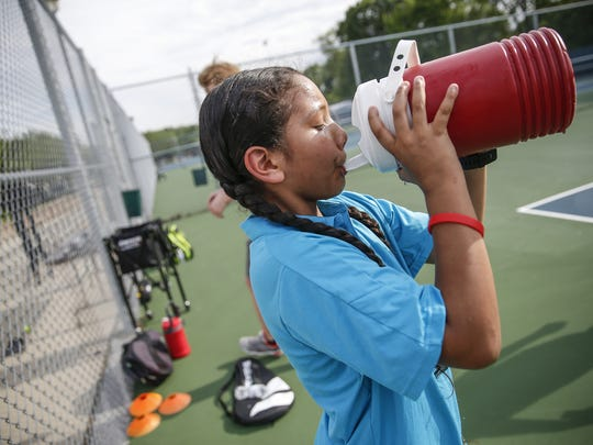"""Rogelio grabs a quick drink after a drill during a National Junior Tennis League (NJTL) of Indianapolis practice at Marian University. """"I don't want to brag about myself but I think I'm a natural athlete,"""" Rogelio said. """"I think it comes easily because of that. But it's very hard."""""""