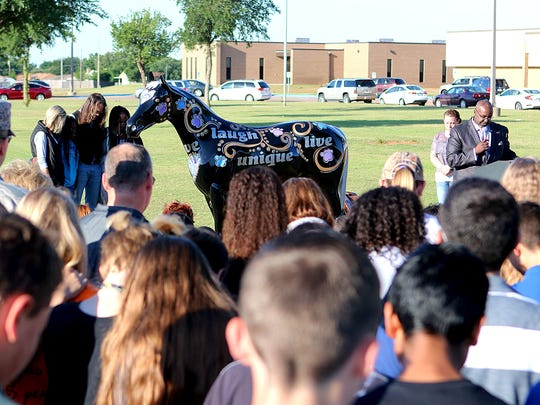 "Pastor Rodney Smith (right) says a prayer of dedication after the unveiling the Mane Event horse ""Forever"" Wednesday morning outside McNiel Middle School."