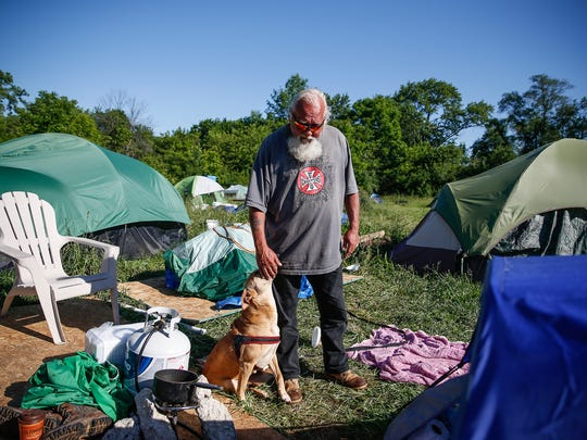 "Tommy Woods, who lives in a tent behind a church on 38th Street, pets his dog, Rose, on Thursday, June 1, 2017. ""She's my guard dog,"" said Woods. ""We hear a bunch of gun shots around here but you ain't walking up on me at night."""