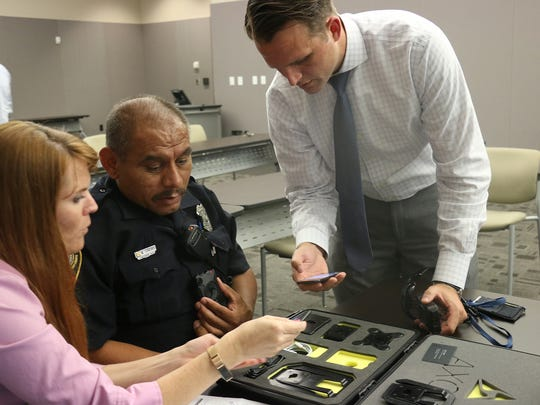 Axon's Marcus Boehler shows Officer Mark Sanchez and City of Franklin Attorney Shauna R. Billingsley what it looks like when a police body camera is switched on.