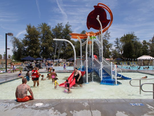 Kids and families cool off in a pool at the Palm Desert