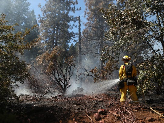 A CalFire firefighter works on one of several small