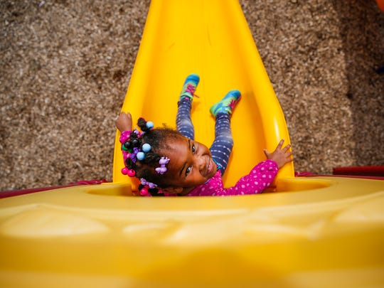 Leilah, 4, daughter of Adrienne Brown, prepares to go down a slide on the playground at Wheeler Mission Center for Women & Children on Wednesday, July 12, 2017.