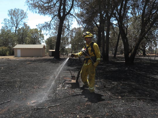 Redding Fire engineer Aaron Dieck puts out hotspots