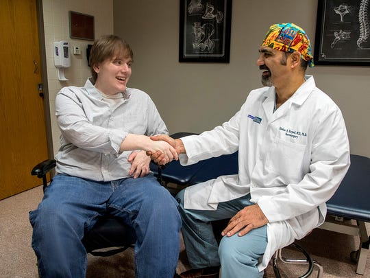 Lucas Lindner shakes hands with Shekar Kurpad, director of the spinal cord injury program at Froedtert & the Medical College of Wisconsin. Lindner, who has regained the use of his arms through an experimental treatment, will throw out the first pitch from his wheelchair at Sunday's Brewers game at Miller Park.