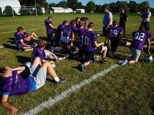 The Baxter Bolts football team huddles after practice