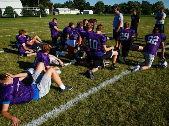 The Baxter Bolts football team huddles after practice