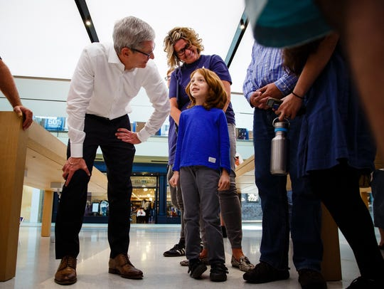 Apple CEO Tim Cook talks with employees and store patrons