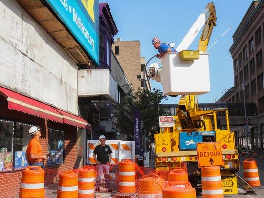 Workers prepare to take down the billboard on the corner