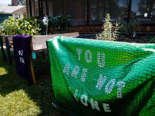 "A banner with the saying ""You are not alone"" hangs on the side of the raised bed gardens outside of Oak Place on Wednesday, Aug. 30, 2017, in Centerville. The center, which opened in 2014, has been held up as a statewide and even national model, but it's on the brink of closing because of financial problems."