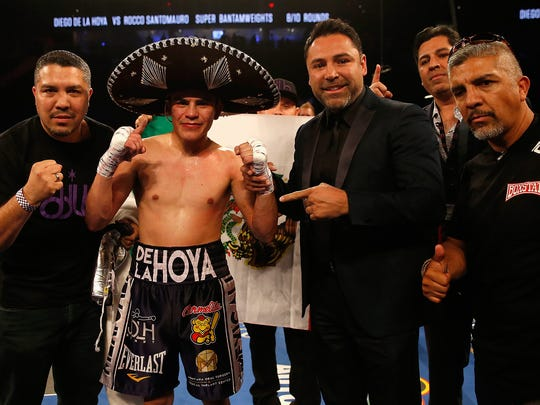 LAS VEGAS, NEVADA - MAY 07:  Diego De La Hoya (2nL) celebrates his TKO win with former professional boxer and founder of Golden Boy Promotions, Oscar De La Hoya (3rd L) during the super bantamweight fight at T-Mobile Arena on May 7, 2016 in Las Vegas, Nevada.  (Photo by Christian Petersen/Getty Images)