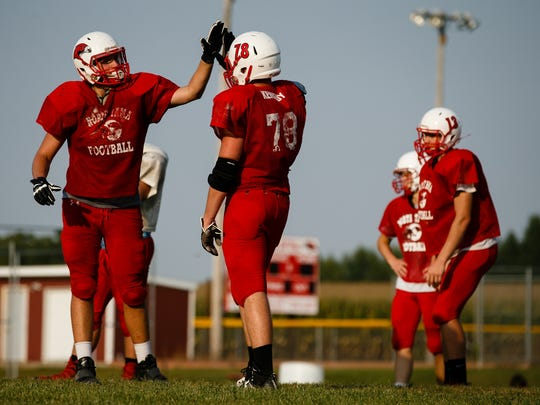 North Tama senior Cory Kennedy, right, gets a high five from a teammate after a drill on Tuesday, Sept. 12, 2017, in Traer. Kennedy is one of Class AÕs best two-way linemen. Instead of spending his last high school summer with friends he followed his families tradition of service and went into the National Guard.