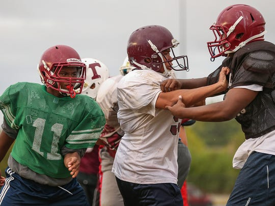 Tindley Tigers clash while running a play during practice at Charles A. Tindley Accelerated School, Indianapolis, Wednesday, Sept. 13, 2017.