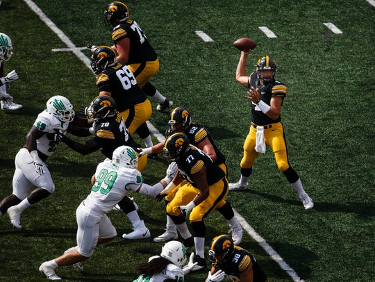 Iowa's Nate Stanley (4) passes the ball during their
