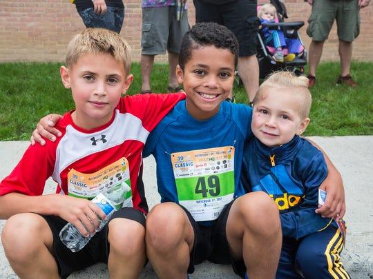Kids' mile boys winner Noah Mellen, center, sits with