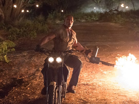 Dwayne Johnson wields a flamethrower in 'Jumanji: Welcome