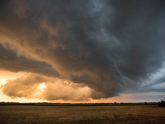 The sun sets behind a shelf cloud associated with a