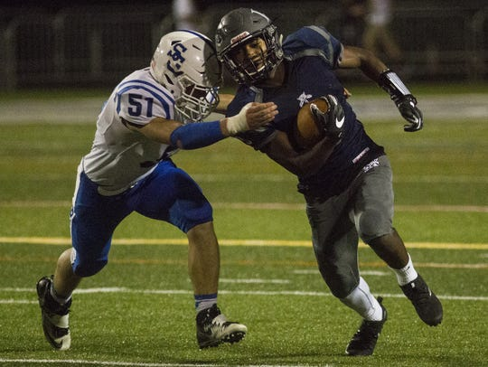 Dallastown running back Nyzair Smith, right, eludes a would-be tackler in this file photo from Dallastown's victory against Spring Grove in September.  The junior broke Dallastown's single-season and single-game rushing records with a 365-yard game against Central York Friday, Oct. 27, 2017.