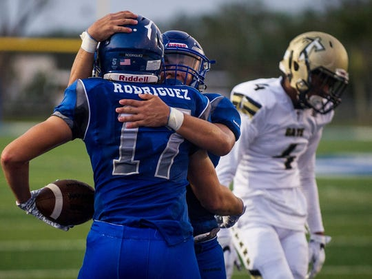 Barron Collier High School wide receiver Logan Rodriguez is hugged by a teammate after scoring the game's first touchdown against Golden Gate High School at Barron Collier on Thursday, September 28, 2017.