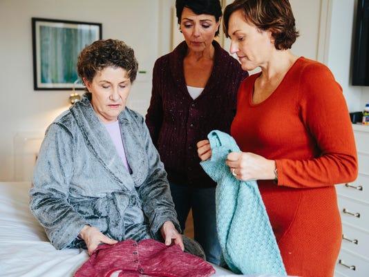 Caregivers prepare to help mom dress.
