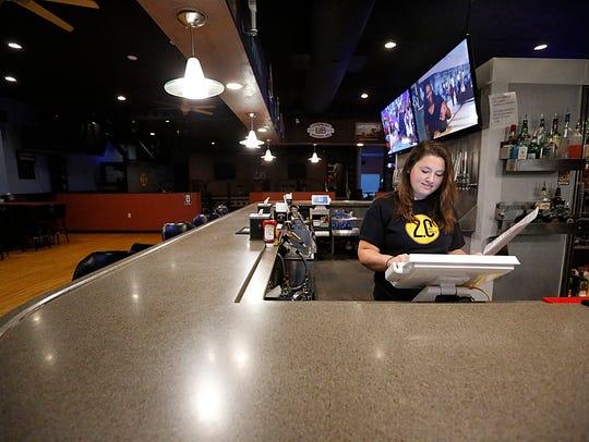 Sam Boda, manager of 2.0 Ale House, enters menu items