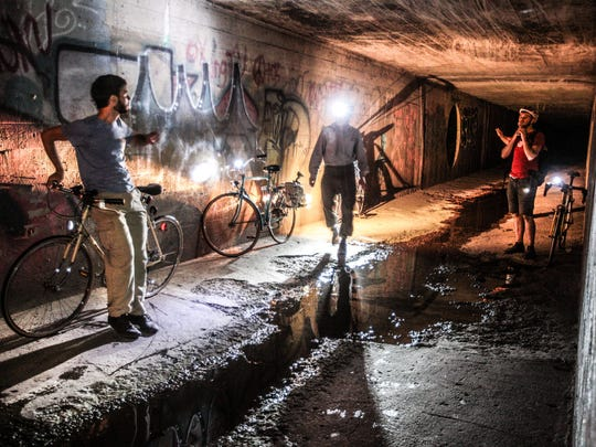 In this 2013 photo, IndyStar reporter Will Higgins, avid bicyclist Jamey McPherson and French visiting artist Florian Riviere are seen at one end of the Pogue's Run tunnel.