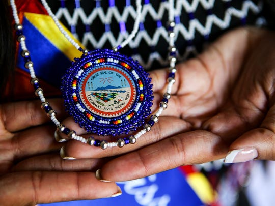 Mariah Jordan Sharpe, who is Mohave, holds a Colorado River Indian Tribes pendant at her Phoenix apartment Oct. 17, 2017. Sharpe was crowned Miss Indian Arizona over the weekend.
